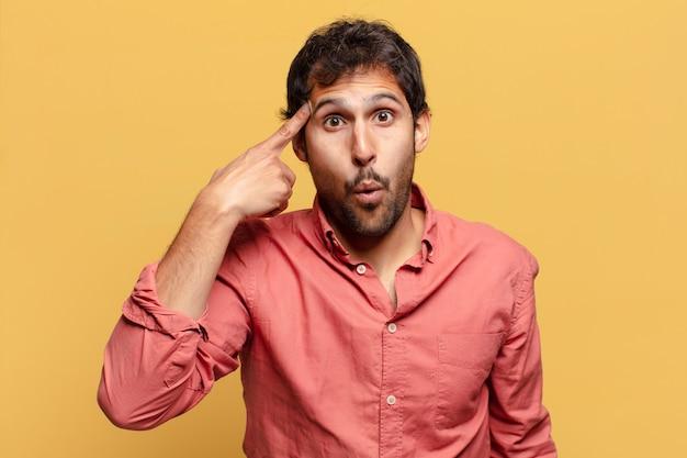 Jonge knappe indiase man. denkende of twijfelende uitdrukking