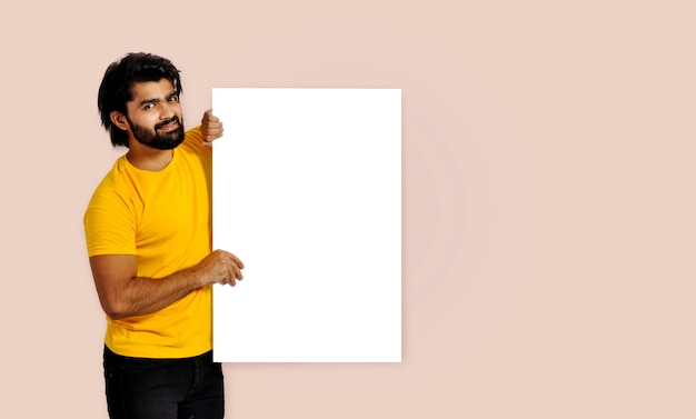 Jonge knappe indiase man die een leeg bord vasthoudt en glimlacht kijkend naar de camera