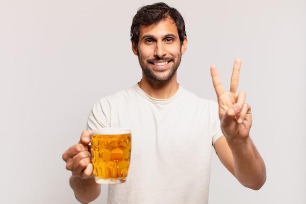 Jonge knappe indiase man die een succesvolle overwinning viert en een biertje vasthoudt