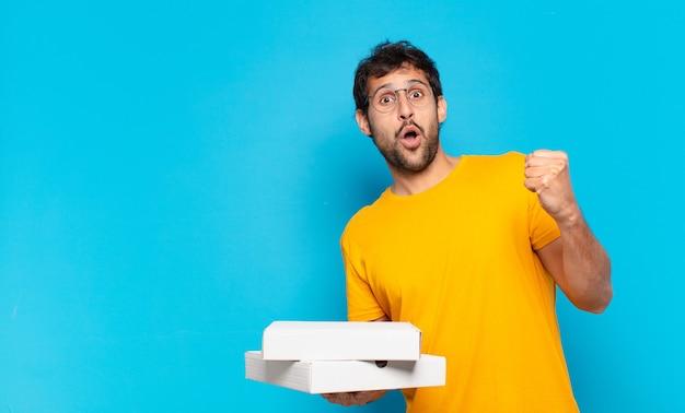 Jonge knappe indiase man die een succesvolle overwinning viert en pizza's meeneemt?