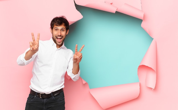 Jonge knappe indiase man die een succesvolle overwinning viert tegen de achtergrond van een gebroken papiergat