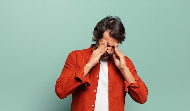 Jonge knappe indiase man die er gestrest en gefrustreerd uitziet, onder druk werkt met hoofdpijn en last heeft van problemen