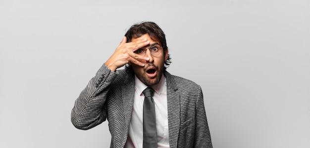 Jonge knappe indiase man die geschokt, bang of doodsbang kijkt, zijn gezicht bedekt met de hand en tussen de vingers gluurt. bedrijfsconcept