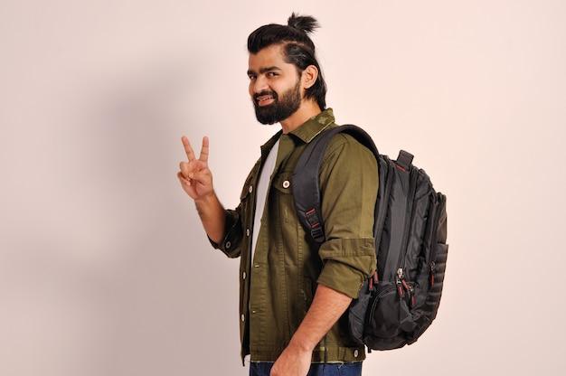 Jonge knappe indiase man die lacht en naar de camera kijkt en laat zien dat vingers een overwinningsteken doen
