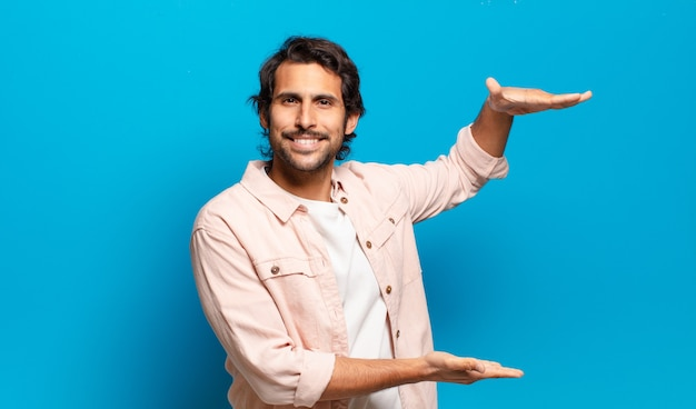 Jonge knappe indiase man die lacht, zich gelukkig, positief en tevreden voelt, een object of concept vasthoudt of toont op kopieerruimte