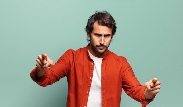 Jonge knappe indiase man die met beide vingers en een boze uitdrukking naar de camera wijst en je vertelt je plicht te doen