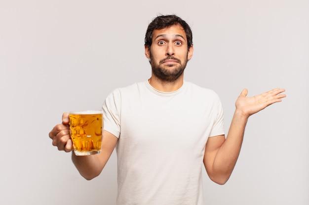 Jonge knappe indiase man die twijfelt of een onzekere uitdrukking heeft en een biertje vasthoudt