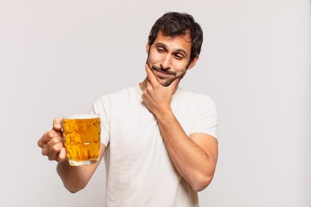 Jonge knappe indiase man die uitdrukking denkt en een biertje vasthoudt