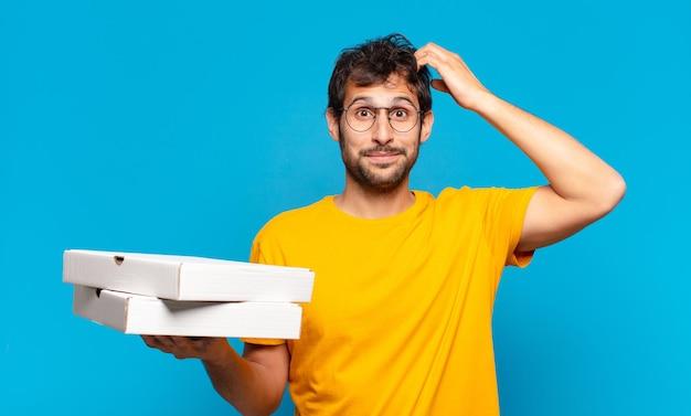 Jonge knappe indiase man die uitdrukking denkt en pizza's meeneemt?