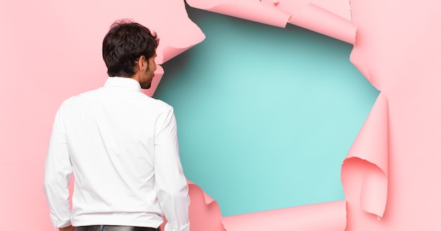 Jonge knappe indiase man die uitdrukking denkt tegen de achtergrond van een gebroken papiergat
