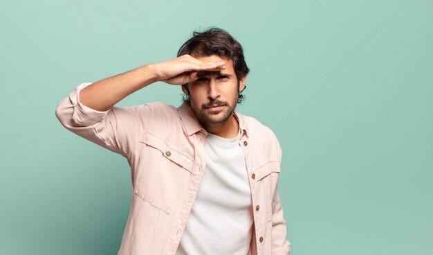 Jonge knappe indiase man die verbijsterd en verbaasd kijkt, met de hand over het voorhoofd ver weg kijkend, kijkend of zoekend
