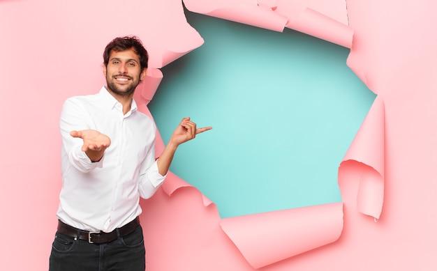 Jonge knappe indiase man die wijst of laat zien tegen de achtergrond van een gebroken papiergat