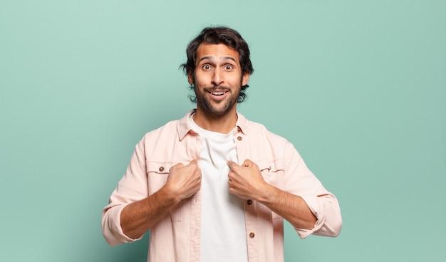 Jonge knappe indiase man die zich blij, verrast en trots voelt en naar zichzelf wijst met een opgewonden, verbaasde blik