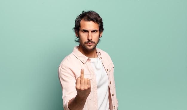 Jonge knappe indiase man die zich boos, geïrriteerd, opstandig en agressief voelt, de middelvinger omdraait, terugvecht