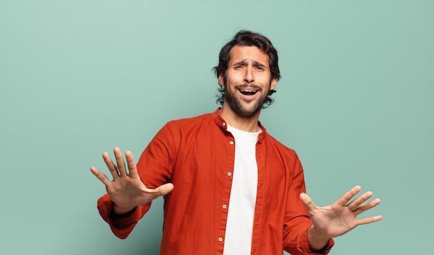 Jonge knappe indiase man die zich doodsbang voelt, zich terugtrekt en schreeuwt van afgrijzen en paniek, reageert op een nachtmerrie