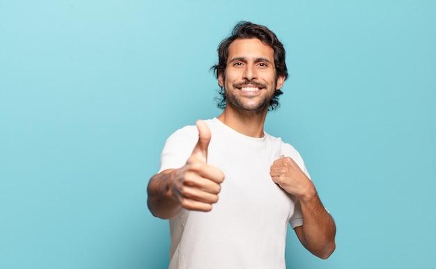 Jonge knappe indiase man die zich trots, zorgeloos, zelfverzekerd en gelukkig voelt en positief glimlacht met zijn duimen omhoog
