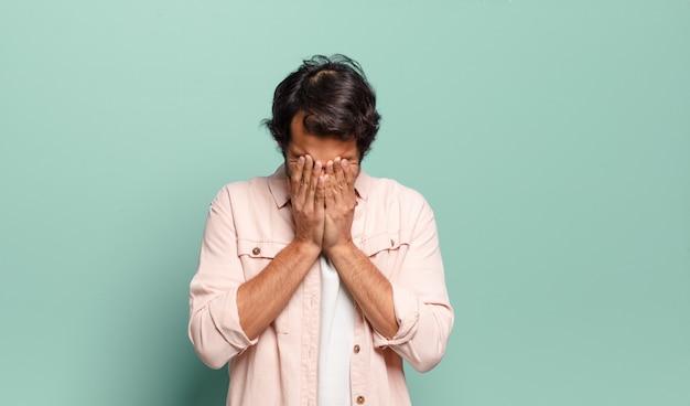 Jonge knappe indiase man die zich verdrietig, gefrustreerd, nerveus en depressief voelt en zijn gezicht met beide handen bedekt
