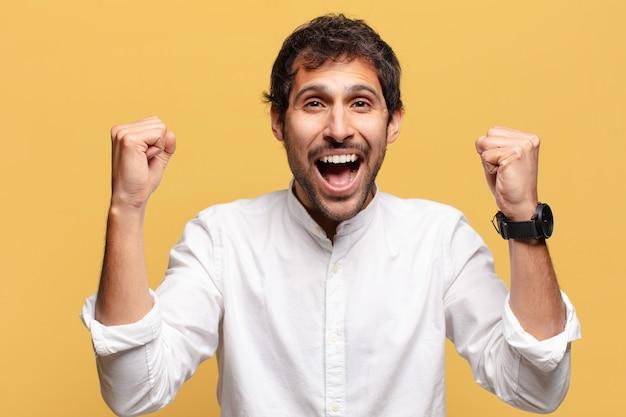 Jonge knappe indiase man. een triomf vieren als een winnaar