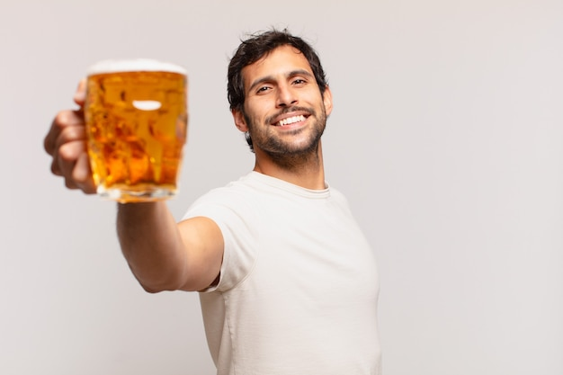 Jonge knappe indiase man gelukkige uitdrukking en met een biertje