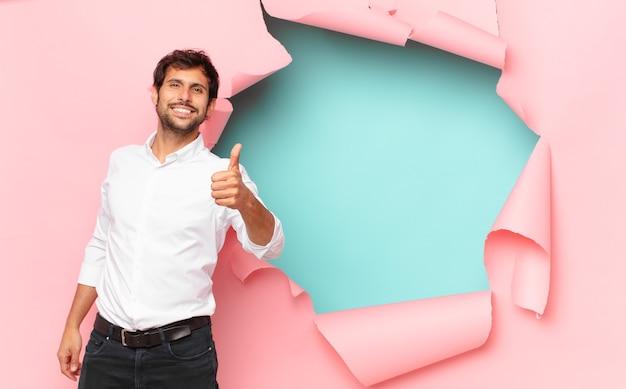 Jonge knappe indiase man gelukkige uitdrukking tegen gebroken papier gat achtergrond