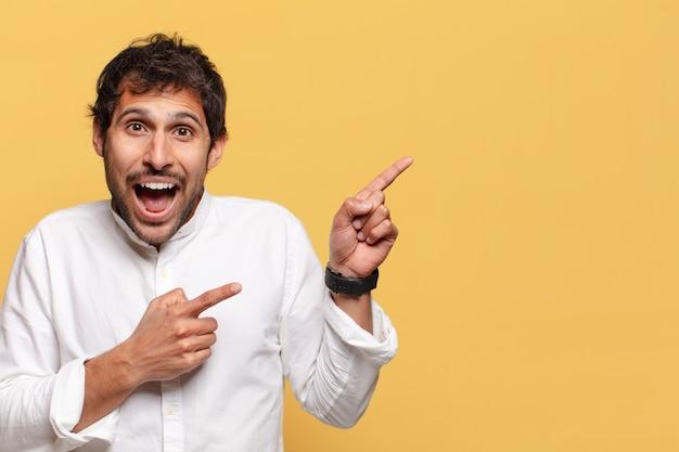Jonge knappe indiase man geschokt of verrast uitdrukking