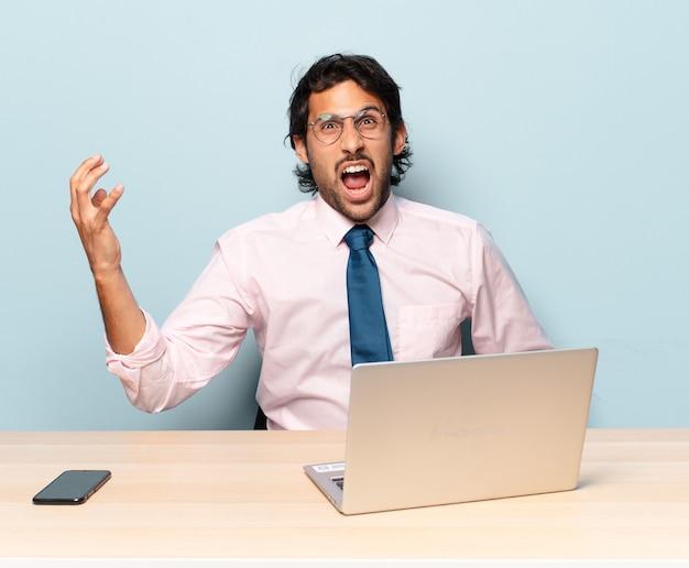 Jonge knappe indiase man kijkt boos, geïrriteerd en gefrustreerd schreeuwend wat er mis is met je