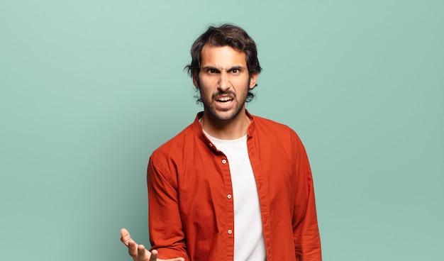 Jonge knappe indiase man kijkt boos, geïrriteerd en gefrustreerd schreeuwend wtf of wat is er mis met je