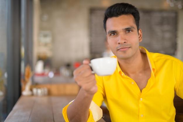 Jonge knappe indiase man koffie drinken bij het raam op de c