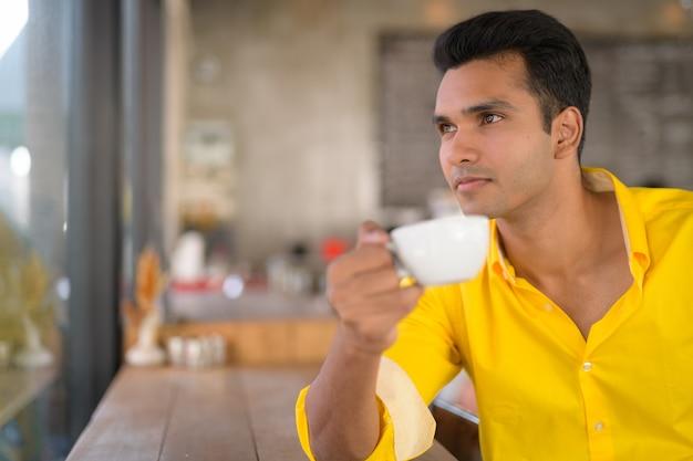 Jonge knappe indiase man koffie drinken terwijl hij uitkijkt thro