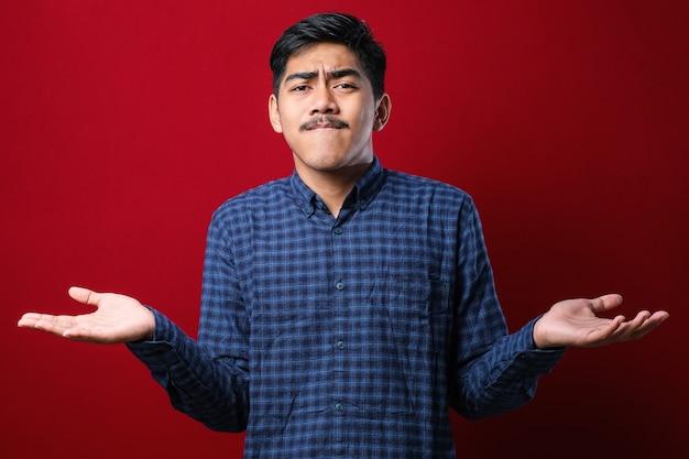 Jonge knappe indiase man met een casual shirt over een rode achtergrond, geen idee en verwarde uitdrukking met opgeheven armen en handen. twijfel concept.