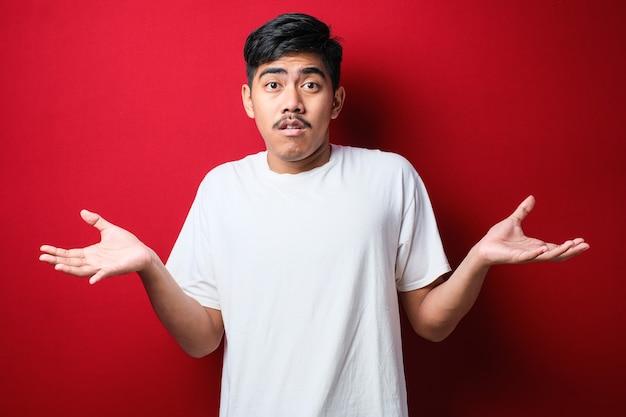Jonge knappe indiase man met een wit t-shirt over een rode achtergrond, geen idee en verwarde uitdrukking met opgeheven armen en handen. twijfel concept.