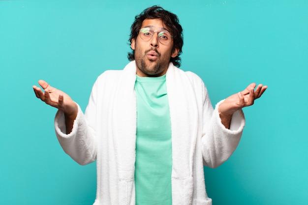 Jonge knappe indiase man met open mond en verbaasd, geschokt en verbaasd met een ongelooflijke verrassing en badjas aan