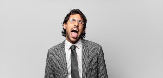 Jonge knappe indiase man met vrolijke, zorgeloze, rebelse houding, grappen maken en tong uitsteken, plezier maken. bedrijfsconcept
