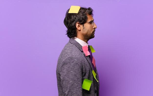 Jonge knappe indiase man op profielweergave die ruimte vooruit wil kopiëren, denken, verbeelden of dagdromen. humoristisch bedrijfsconcept