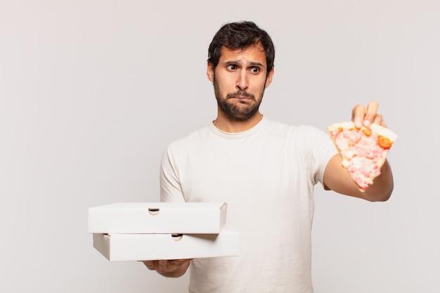 Jonge knappe indiase man twijfelt of onzekere uitdrukking en houdt pizza's mee