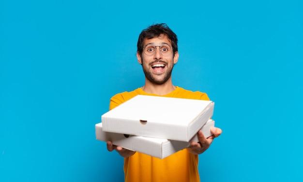 Jonge knappe indiase man verraste uitdrukking en hield afhaalpizza's vast