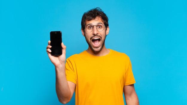 Jonge knappe indiase man verraste uitdrukking en houdt een mobiele telefoon vast