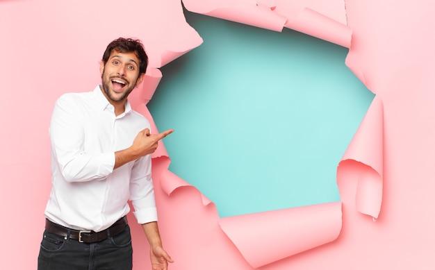 Jonge knappe indiase man verraste uitdrukking tegen gebroken papieren gat in de muur