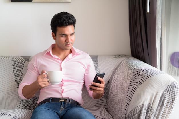 Jonge knappe indiase zakenman koffie drinken tijdens het gebruik van telefoon thuis