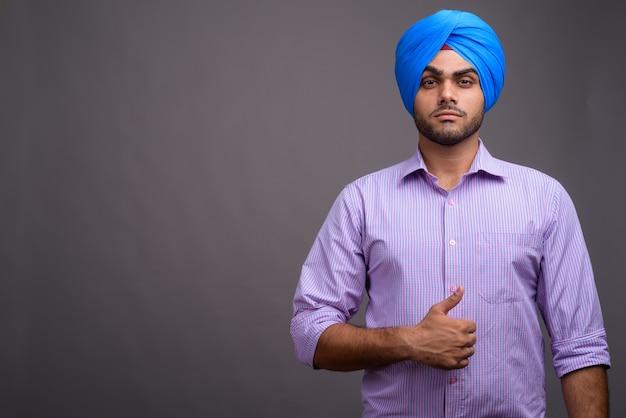 Jonge knappe indiase zakenman tulband dragen tegen grijze muur