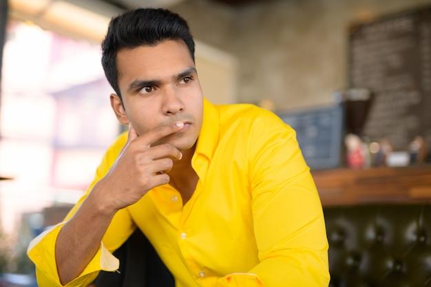 Jonge knappe indier die en bij de koffiesho denken zitten