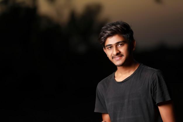 Jonge knappe indische jongen die zwarte t-shirt draagt