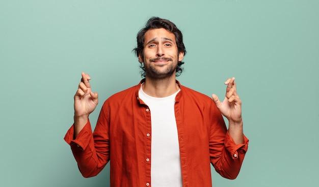 Jonge knappe indische man die lacht en angstig beide vingers kruist, zich zorgen maakt en geluk wenst of hoopt