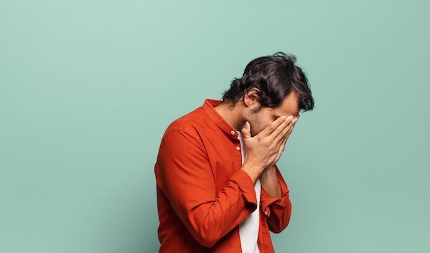 Jonge knappe indische man die ogen bedekt met handen met een droevige, gefrustreerde blik van wanhoop, huilend, zijaanzicht