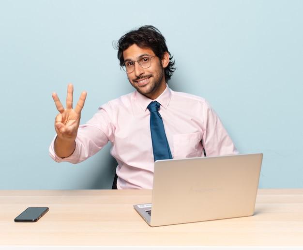 Jonge knappe indische mens die en vriendelijk glimlacht kijkt, nummer drie of derde met vooruit hand toont, aftellend. bedrijfs- en frelancer-concept