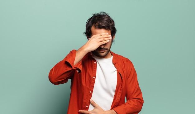 Jonge knappe indische mens die gestrest, beschaamd of overstuur kijkt, met hoofdpijn, gezicht bedekt met hand