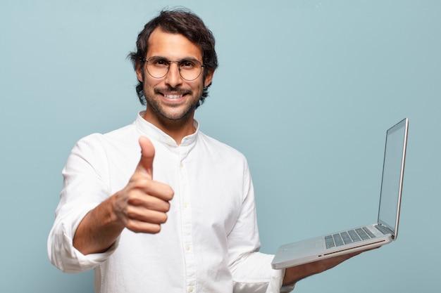 Jonge knappe indische mens die laptop houdt