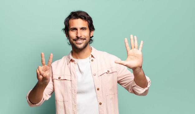 Jonge knappe indische mens die vriendelijk glimlacht kijkt, nummer zeven of zevende met vooruit hand toont, aftellend