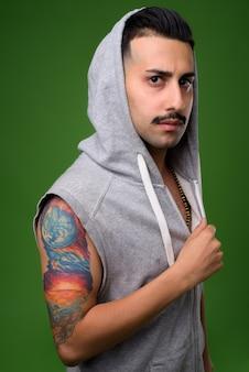 Jonge knappe iraanse man met snor op groen