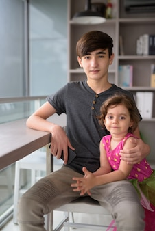 Jonge knappe iraanse tiener met zusje thuis ontspannen